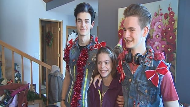Adam Sturgeon, Annabella Milne, and Matthew Milne showing off their recycled wrapping paper vests.