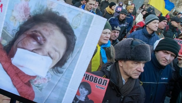 A protester holds pictures of journalist Tetyana Chornovil, who was beaten and left in a ditch hours after publishing an article on the assets of top government officials, during a protest rally in Kyiv on Dec. 26.