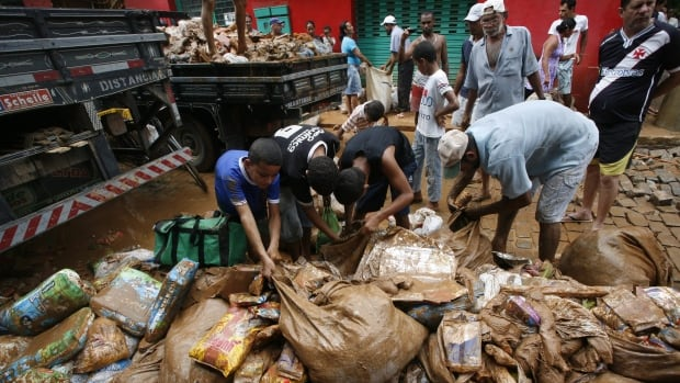 People collect discarded food drenched in mud and rain, outside a supermarket in the municipality of Itaguacu, Espirito Santo state, Brazil, on Dec. 25, 2013.