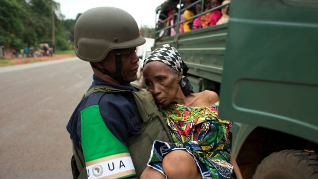 An African Union peacekeeper carries an elderly Cameroonian woman, too frail to walk, to a military vehicle shuttling Cameroonian citizens to the airport for an evacuation flight, in Bangui, Central African Republic on Dec. 27, 2013.