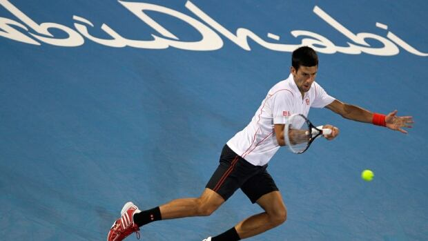 Novak Djokovic of Serbia returns the ball to Jo-Wilfried Tsonga of France during the second day of the Mubadala World Tennis Championship in Abu Dhabi, United Arab Emirates on Friday.