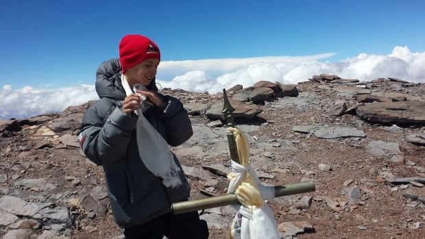 Tyler Armstrong, from Southern California, is shown standing by a cross on the summit of Aconcagua Mountain in Argentina. The nine-year-old boy has become the youngest person in recorded history to reach the summit of Argentina's Aconcagua mountain.