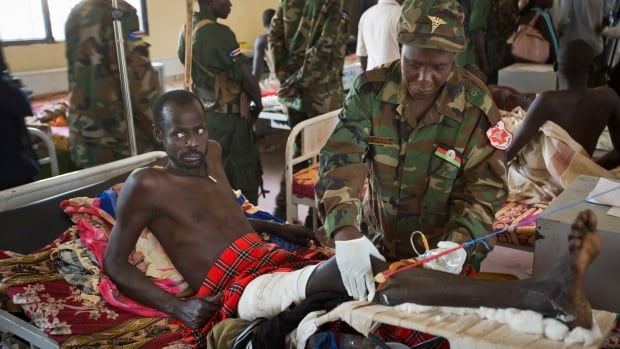 A patient is treated by a military doctor in a ward of mainly soldiers with gunshot wounds. More fighting is expected in the world's newest country.