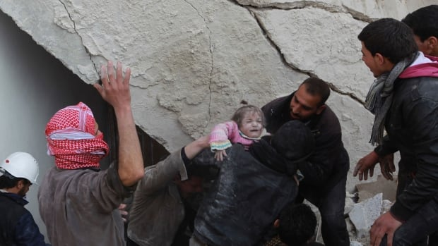 A child is rescued from under the rubble of a collapsed building in the Maysar neighbourhood of Aleppo December 28, 2013. The building collapsed after two air strikes in the neighbourhood by forces loyal to Syria's President Bashar al-Assad on Saturday, activists said.