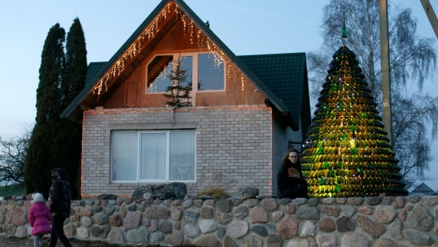 Goda Valukonyte  poses by the bottle Christmas tree in Agariniu village, Lazdijai district, some 176 kilometers from Vilnius, Lithuania .