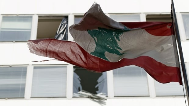 A tattered Lebanon flag flies last week in front of damaged windows caused by a deadly bomb blast in Beirut that was blamed on tensions caused by the civil war in neighbouring Syria. Lebanese forces fired on Syrian aircraft that violated the country's airspace on Monday.