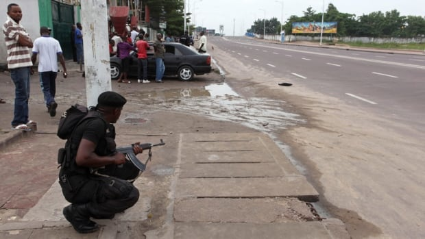 A Congolese security officer takes position to secure the street near the state television headquarters in the capital Kinshasa on Monday. Armed youths tried to seize the TV station, the airport and a military barracks before being repulsed by troops, in clashes the government said killed 103 people, including eight soldiers.
