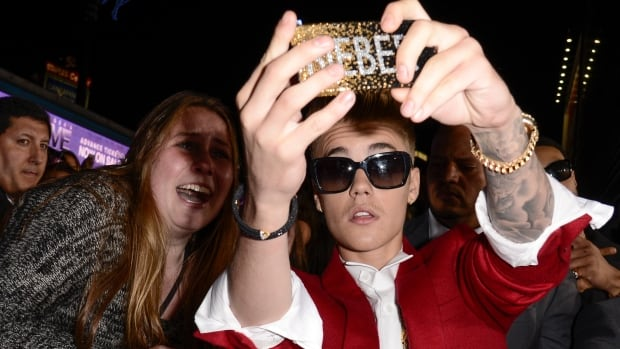 Justin Bieber takes a selfie with a fan at the premiere of the feature film Justin Bieber's Believe at Regal Cinemas L.A. Live in Los Angeles.