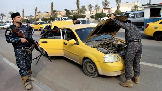 Iraqi federal policemen search a car at a checkpoint in Basra, Iraq's second-largest city, 550 kilometres southeast of Baghdad, Iraq, on Thursday.