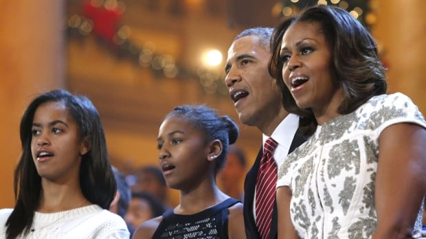 U.S. President Barack Obama, his wife Michelle and their daughters Malia and Sasha sing Christmas carols in Washington television program last month. A book of personal White House family photos was mistakenly sent to a suburban Chicago woman as a Christmas gift, the White House confirmed.