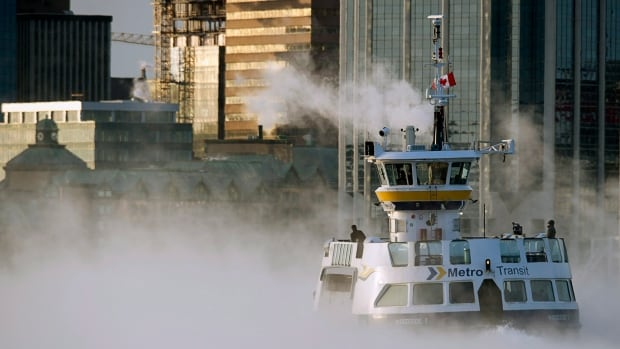 A Metro Transit ferry crosses the harbour through sea smoke. The ferry connects downtown Halifax with downtown Dartmouth.