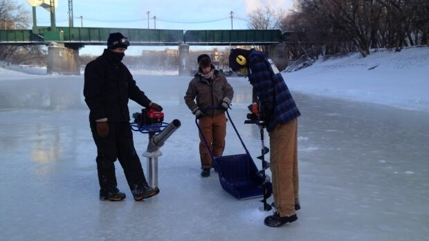 Crews at The Forks dig into the river to determine ice thickness in Winnipeg on Thursday.