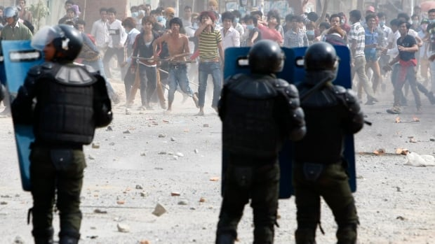 Cambodia garment workers throw stones at riot police during a strike near a factory on the Stung Meanchey complex on the outskirts of Phnom Penh on  Jan. 3, 2014.  At least three people were killed when police opened fire to break up a protest by striking garment workers demanding a doubling of the minimum wage, police and human rights workers said.