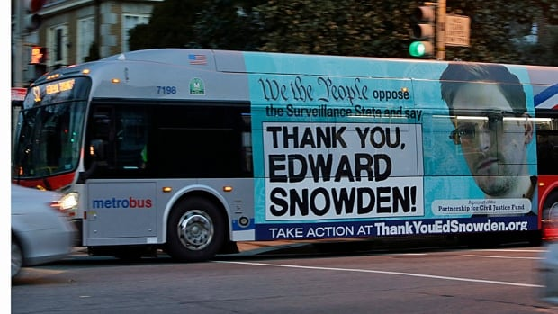 A Washington Metro bus is shown here in December with an Edward Snowden sign on its side. Meanwhile, a White House-appointed panel proposed curbs on some key NSA surveillance operations, putting the ball in Barack Obama's court.