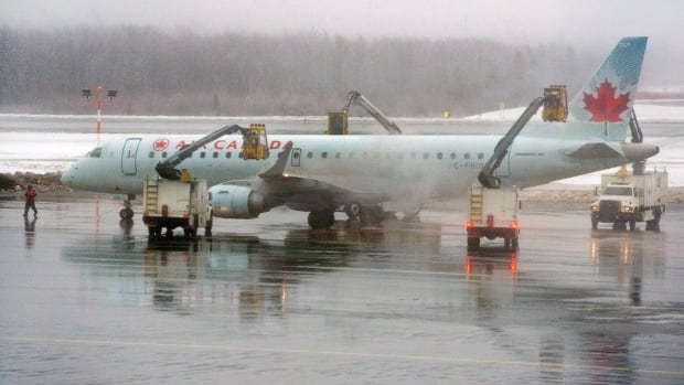 An Air Canada jet is de-iced at Halifax Stanfield International Airport as travellers continue to face delays and cancellations in the eastern seaboard due to a massive winter storm.