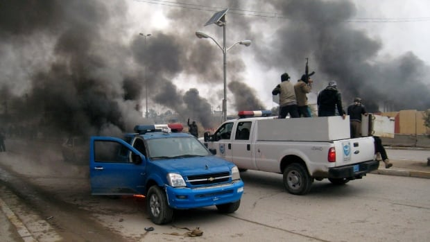 Al-Qaeda-linked fighters patrol in a commandeered police truck passing burning police vehicles in front of the main provincial government building, in Fallujah, 65 kilometres west of Baghdad, Iraq, on Jan. 1, 2014.