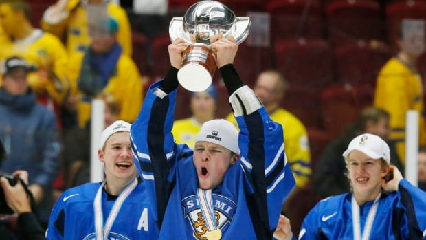 Finland's Mikko Lehtonen celebrates with the trophy after his team defeated Sweden in overtime for gold at the world juniors in Malmo, Sweden on Sunday.