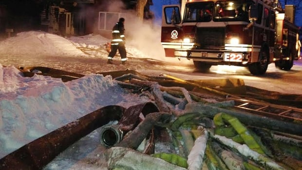 Ice-encrusted hoses lie on the street after firefighters extinguished flames at a house on Edderton Bay in Winnipeg on Monday.