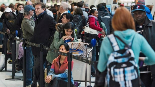 Frustrated passengers line up during flight delays and cancellations due to extreme cold weather and wind chill at Pearson International Airport in Toronto on Tuesday.