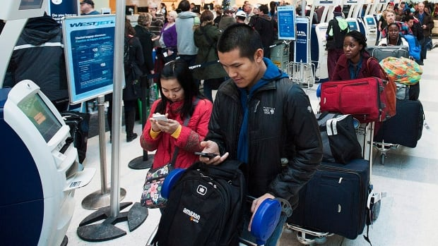 Passengers line up during flight delays and cancellations due to extreme cold weather at Pearson International Airport in Toronto on Tuesday. A group stop order was in place but lifted later in the morning.