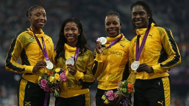Sherone Simpson, second from the left, pose for photos after capturing the silver medal in the Women's 4x100 relay at the 2012 London Olympic games.