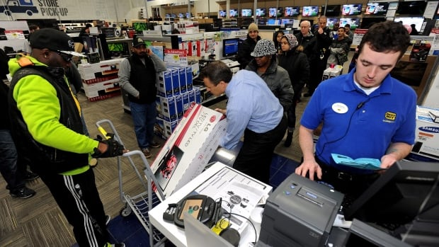 Best Buy employee Christopher Gervais, right, rings up a 32-inch LED TV in Dunwoody, Ga. in November. A last minute surge amid deep discounts helped boost U.S. holiday sales.