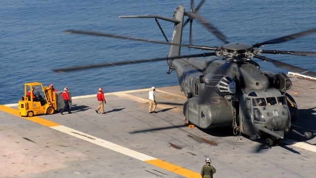 An MH-53E Sea Dragon helicopter is loaded with supplies on board a U.S. aircraft carrier. A similar helicopter was on a training flight when it crashed into the Atlantic Ocean near Fort Story, about 240 kilometres south of Washington, according to the U.S. navy.