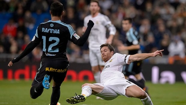 Real Madrid midfielder Xabi Alonso slide tackles Celta de Vigo midfielder Rafinha during league-leading Madrid's recent win over its Spanish league opponents.