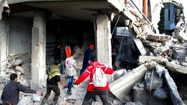 In this photo released by the Syrian official news agency SANA, Syrian citizens and Red Crescent workers look for  victims at site where a car bomb has exploded near a school at al-Kaffat village in the central Hama province on Thursday.