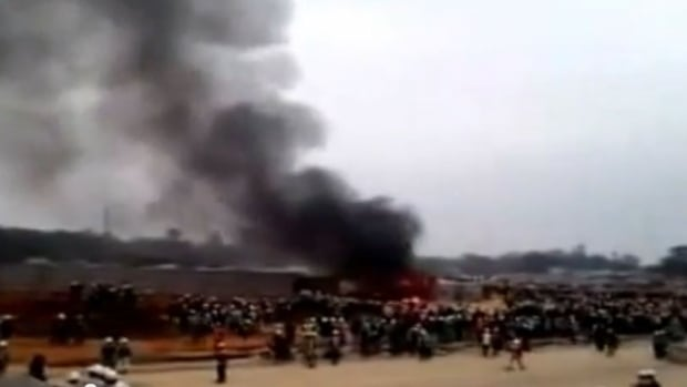 Smoke rises as workers scuffle with police at a building site for a Samsung factory in Vietnam.