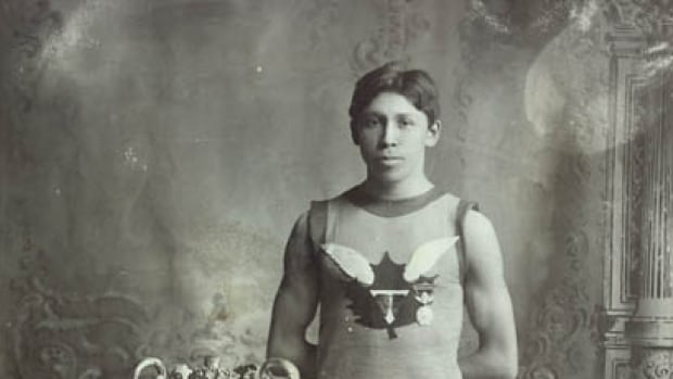 Legendary Onondaga runner Tom Longboat stands next to trophy.