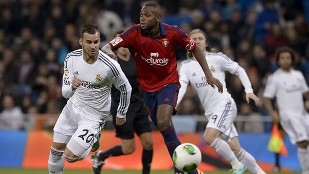 Real Madrid's Jese Rodriguez Ruiz, left, vies with Osasuna's Raoul Loe during the match at the Santiago Bernabeu stadium in Madrid on January 9, 2014.