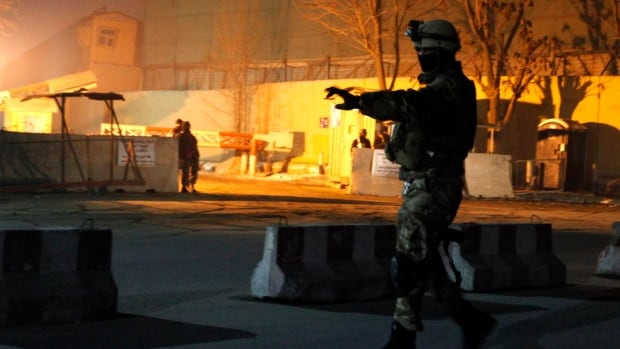 An Afghan security personnel keeps watch near the site of an explosion in Kabul. Relations with the U.S. were further strained Friday when U.S. forces accidentally shot an Afghan boy.