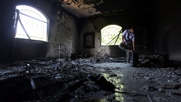 In this file photo from Sept. 13, 2012, A Libyan man investigates the inside of the U.S. Consulate after an attack that killed four Americans on Sept. 11, 2012, in Benghazi, Libya. The Obama administration for the first time on Friday identified two militant groups in Libya as being allegedly involved in the attack.