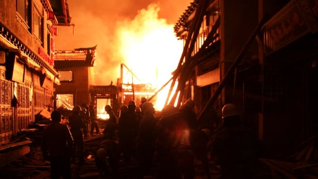 Firefighters fortify a wooden building while a fire ravages ancient Dukezong town in Shangri-la county, in southwestern China's Yunnan province on Jan. 11, 2014.