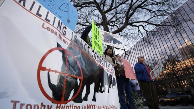 ProtestErs gather holding signs near the Dallas Convention Center where the Dallas Safari Club was holding its weekend show and auction on Saturday.