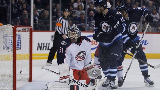 Columbus Blue Jackets goaltender Curtis McElhinney (31) and Winnipeg Jets' Andrew Ladd (16) watch as Jets' Tobias Enstrom's (39) shot from the point goes in during second period NHL action in Winnipeg on Saturday.