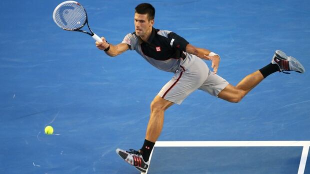 Three-time defending champion Novak Djokovic hits a shot in Monday's 6-5, 7-6, 6-1 win over Lukas Lacko at Melbourne Park.