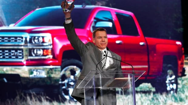 General Motors executive chief engineer Jeffrey Luke holds up the North American Truck of the Year award after the Chevrolet Silverado won at the North American International Auto Show. Paul Sancya/The Associated Press
