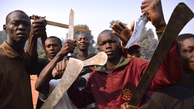 Men brandish machetes and knives to threaten Muslim people in Bangui, Central Africa Republic on January 12, 2014. Reports of cannibalism emerged in the desperately poor country after a Muslim man was allegedly killed by a Christian mob and eaten by one of them.