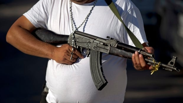 A man belonging to a self-defense group  holds an AK-47 as he stands at a checkpoint in Antunez,  Michoacan State, Mexico, Saturday, Jan. 11, 2014.