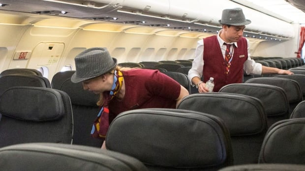 Air Canada Rouge flight attendants check through a plane at Toronto's Pearson Airport on June 25, 2013.
