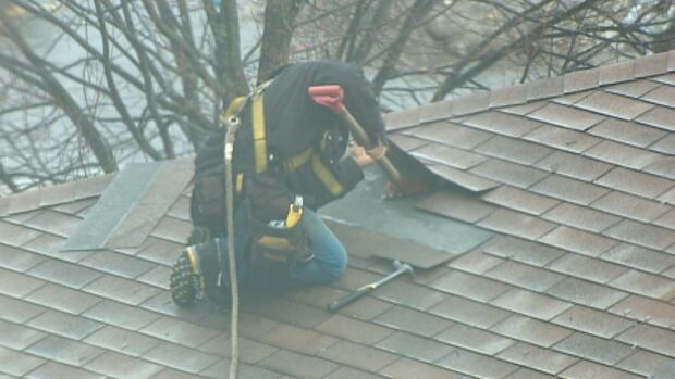 A roofer battens down the shingles in Halifax Tuesday.