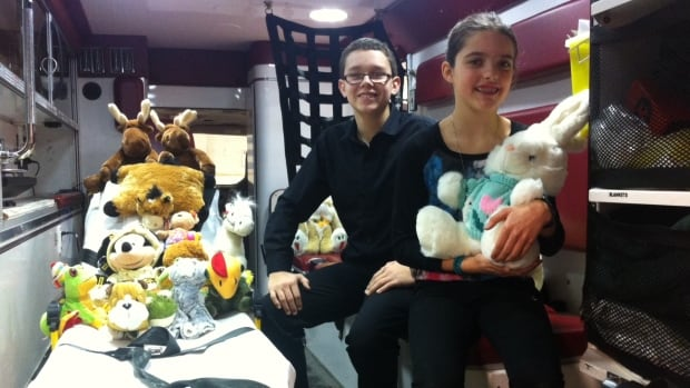 Cameron Houle, left, and Madison Vanderhooft with some of the 140 stuffed animals they delivered to the Winnipeg Fire Paramedic Service on Tuesday. The toys will be offered to children who are riding in an ambulance.