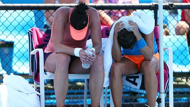 Eva Hrdinova of the Czech Republic and Paula Ormaechea of Argentina feel the heat during a doubles match on January 16, 2014 in Melbourne, Australia.