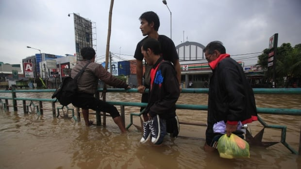 Residents cling to a road divider in an attempt to avoid the flood waters in Jakarta on Jan. 13, 2014. According to local media, floods caused by monsoon rains have forced thousands of people to flee their homes in Indonesia's capital, with the depth of flood waters varying from 50 centimetres to 2 meters.