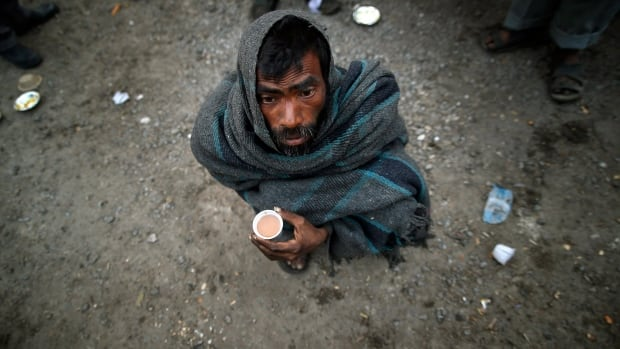 A homeless man holds a cup of tea given to him out of charity on a winter morning in New Delhi this week.