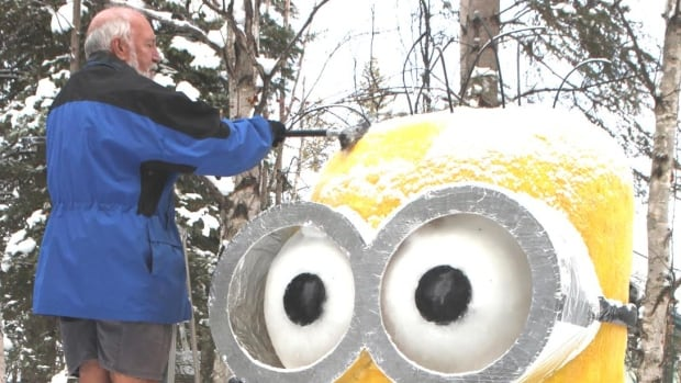 Parkland Beach resident Laurence Rooney brushes snow from his snow sculpture Minion.