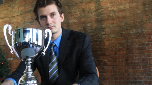 McMaster MBA student Matt Wilusz helped lead the DeGroote team to the 2014 MBA Games title earlier this year in Toronto. Here, he shows off the Queen's Cup, which the team will defend at the games next year in Hamilton.