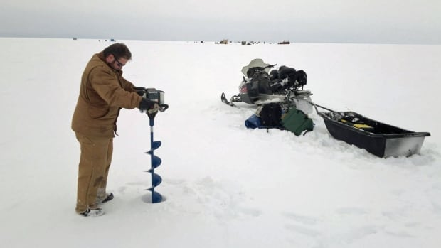 An angler makes a hole with an ice auger in preparation for fishing on Black Bay in northwestern Ontario.